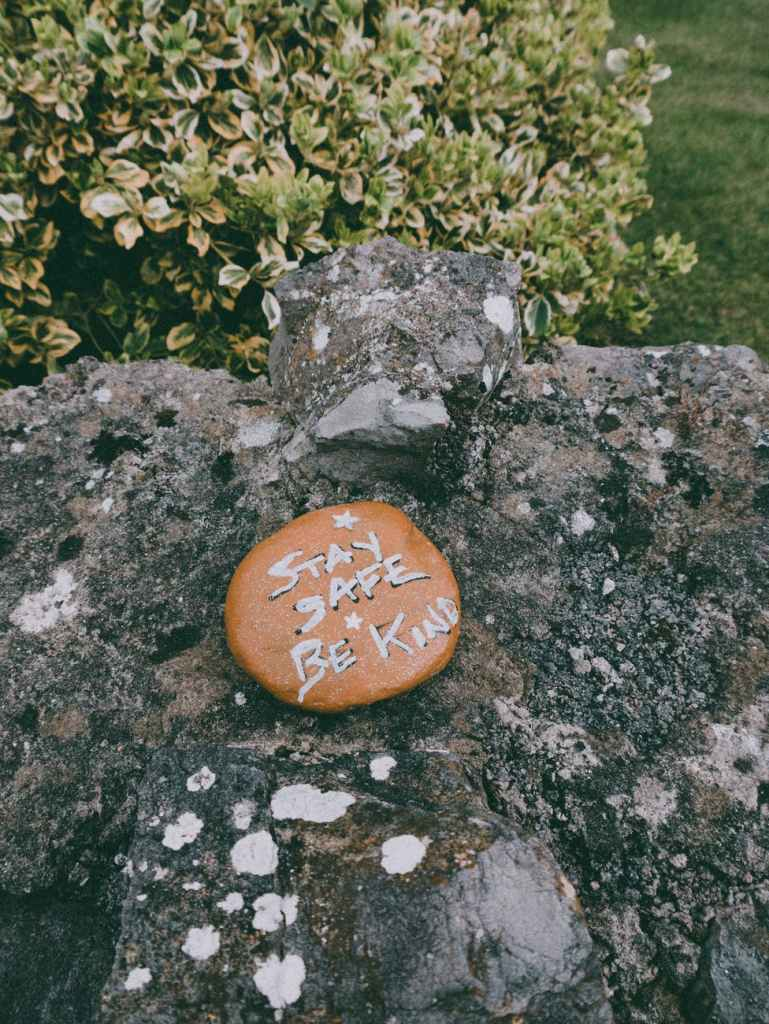 A smooth brown pebble is placed on a larger rock formation in the midst of green bushes and shrubs. On the round pebble are the following words (painted in white) - Stay Safe Be Kind. There is a star painted on the top of these words