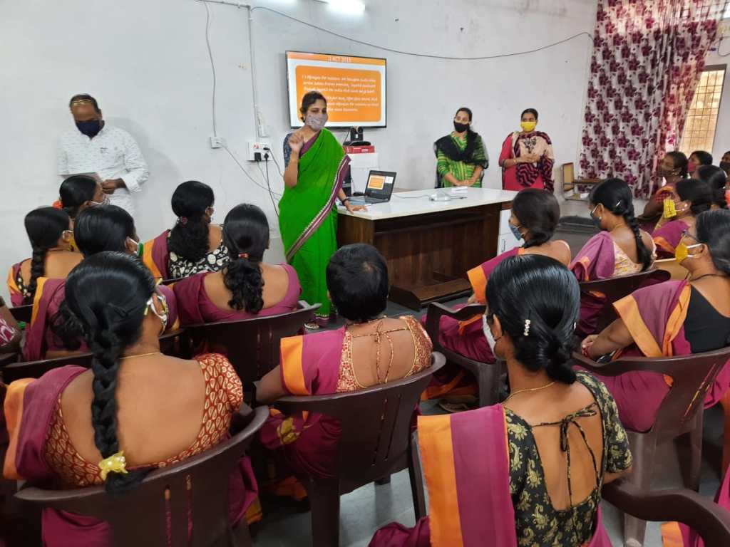 You can see the backs of women in pretty blouses and saris, and a woman in green sari in the front. She is explaining things, there is a laptop and on the wall, at TV, on which the contents of the slides from the laptop are shared