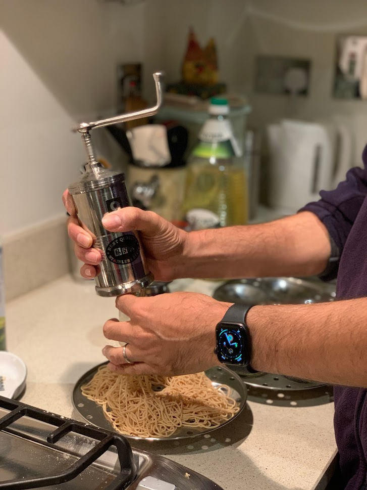 You can see a man's hands holding an Indian device to make string hoppers and in the back are various things - slightly blurred images of a bottle of oil and egg holder